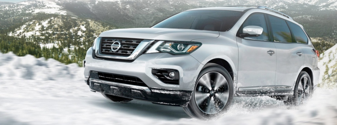 Exterior view of a silver 2019 Nissan Pathfinder driving through the snow