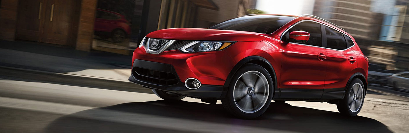 Exterior view of a red 2019 Nissan Rogue Sport driving down a city street