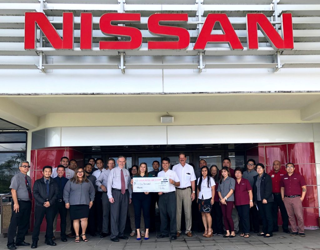Photo of the staff at Nissan Guam presenting Manelu with a donation check