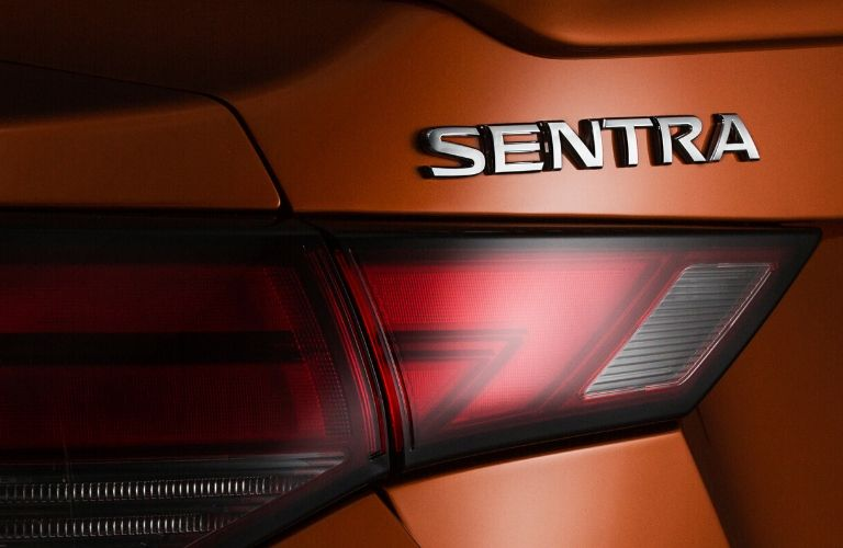 Closeup exterior view of the driver's side taillight and Sentra badge on an orange 2020 Nissan Sentra