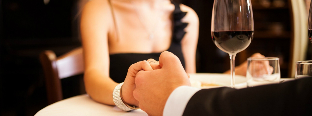 Man Holding Hands with His Girlfriend at Dinner