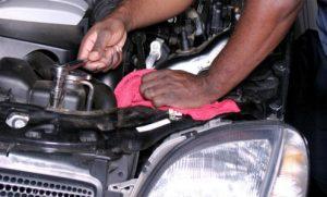 mechanic checking engine oil level