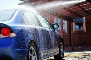 person washing a car with pressure water
