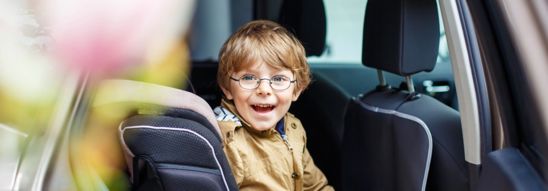 Young toddler boy sitting in car and smiling