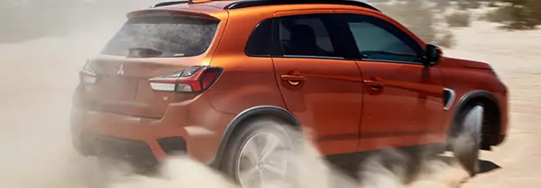 orange mitsubishi outlander sport on dirt road