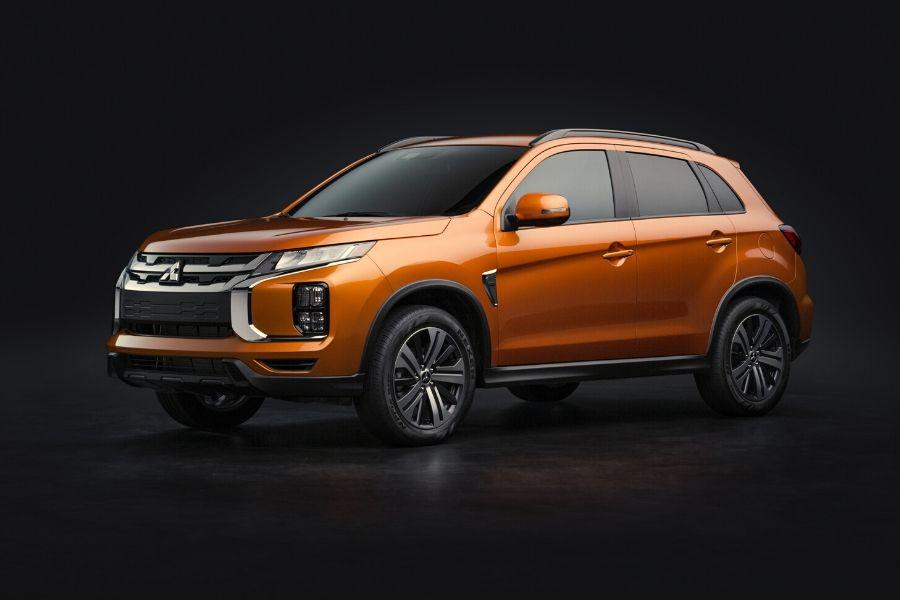 Orange 2020 Mitsubishi Outlander exterior front driver side with black background