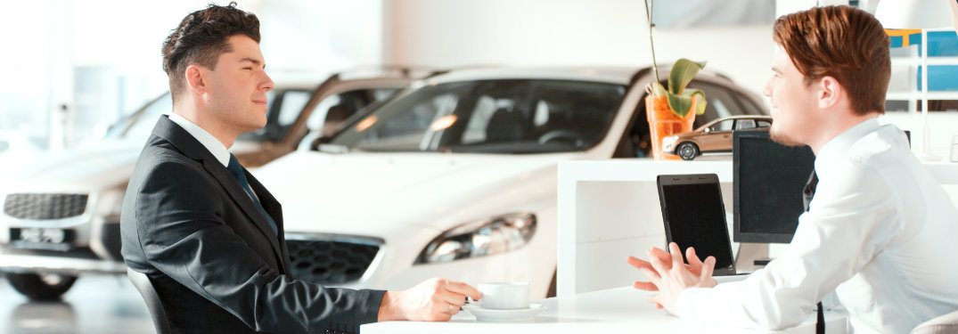 two men at a desk at a car dealership