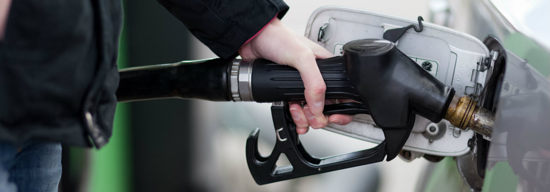 person holding gas pump nozzle in gas tank entry