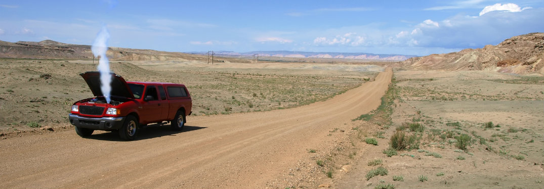 red truck on dirt road with smoking engine