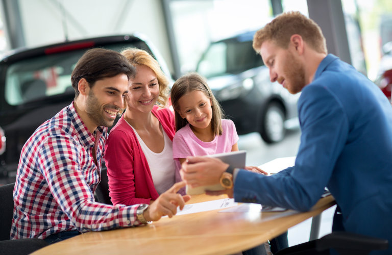 family looking at tablet in car dealership
