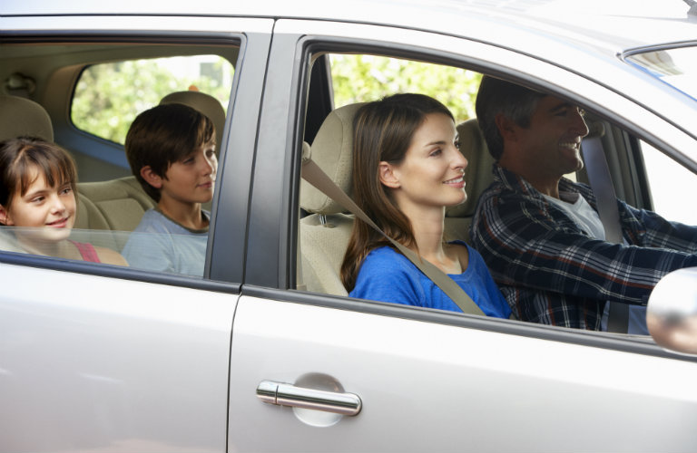 family smiling while sitting in silver car