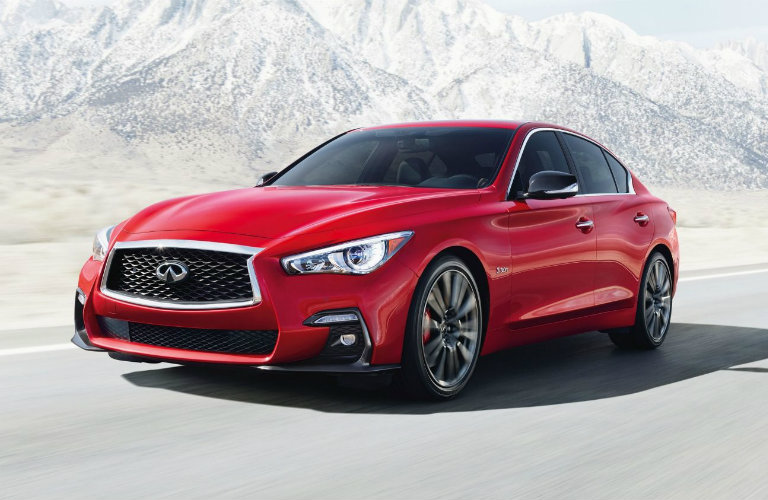 Exterior view of a red 2019 INFINITI Q50 driving down a mountain highway