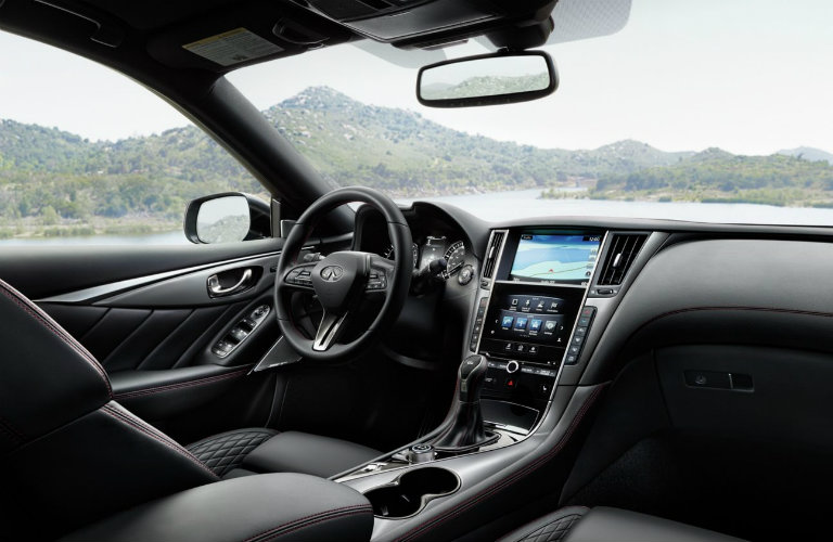 Interior view of the black steering wheel, black seating, and touchscreen inside a 2019 INFINITI Q50