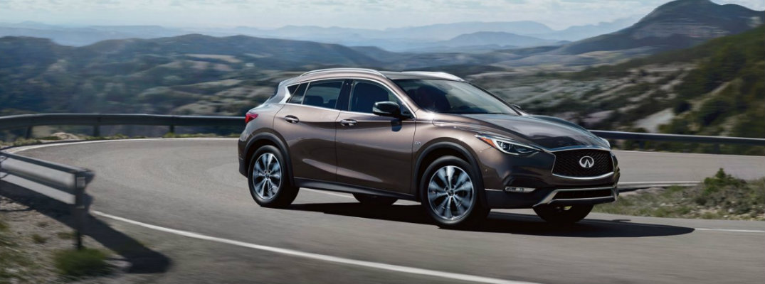 Exterior view of a bronze 2019 INFINITI QX30 driving down a winding road