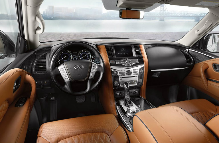 Interior view of the light brown front seating, black steering wheel, and touchscreen inside a 2019 INFINITI QX80