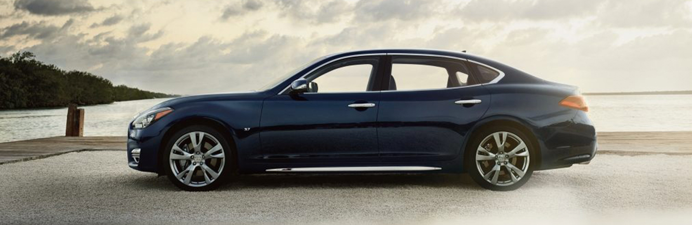 Exterior view of a blue 2019 INFINITI Q70L parked near a large body of water