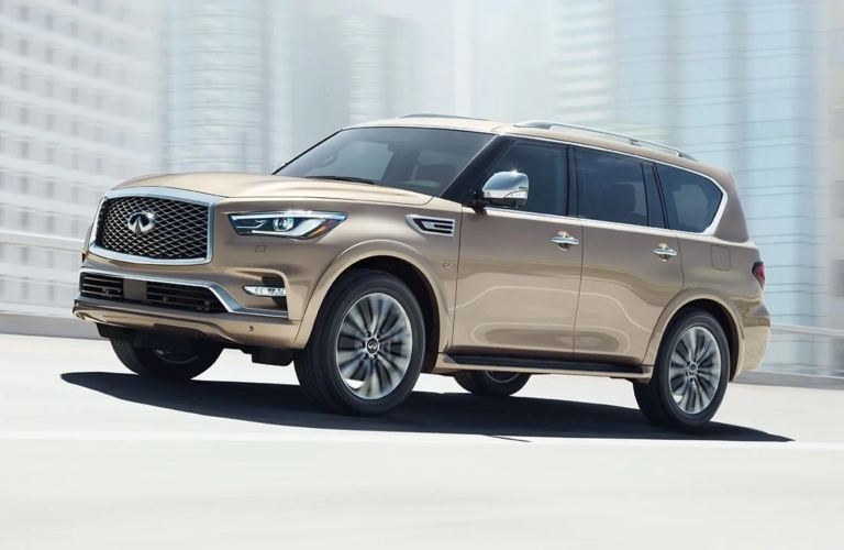 Exterior view of a tan 2019 INFINITI QX80 driving down a city street