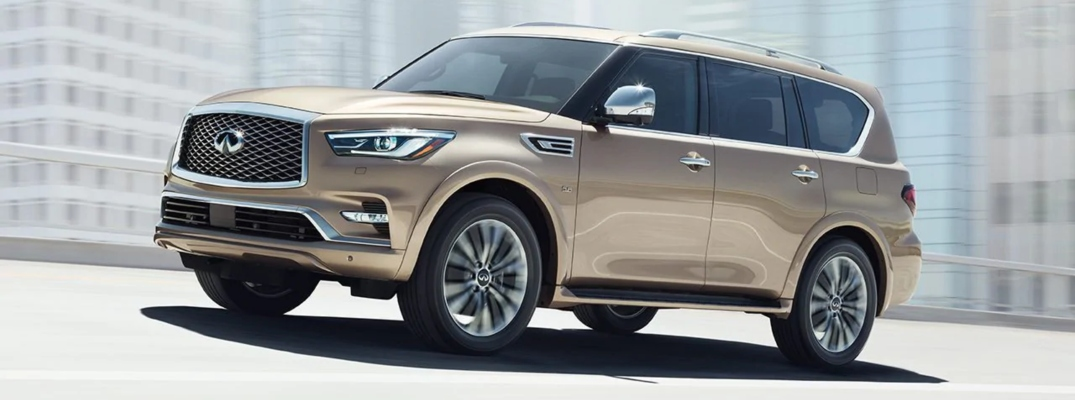Exterior view of a bronze 2019 INFINITI QX80 driving down a city street