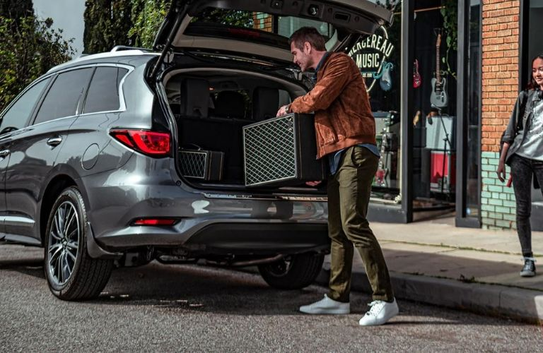 Image of a man loading equipment into the back of a gray 2020 INFINITI QX60