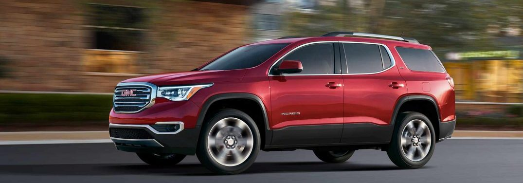 Driver's side profile of the 2018 GMC Acadia with a blurry background