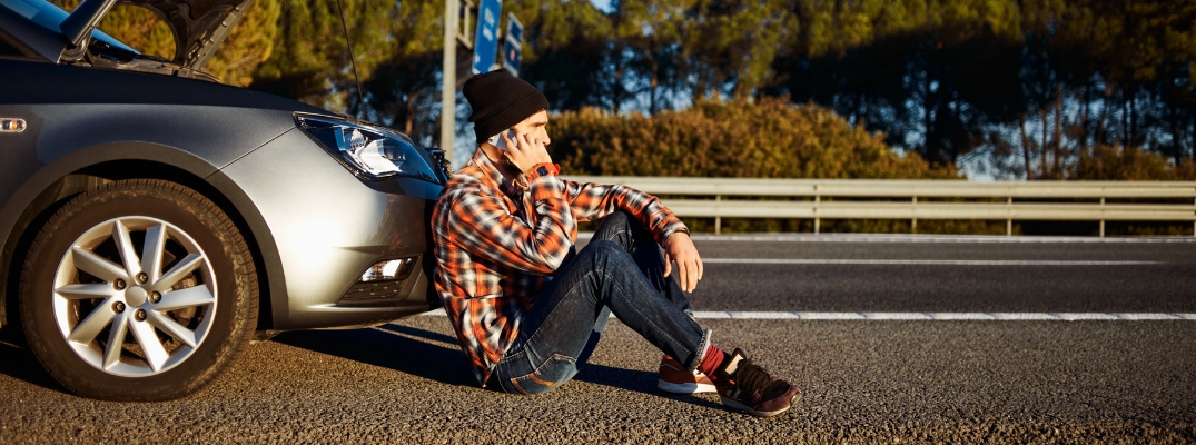 Man talking on the phone and sitting in front of vehicle