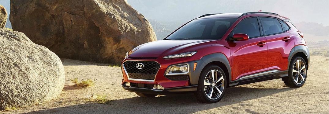 2020 Hyundai Kona red exterior front fascia driver side parked to right of large desert boulders