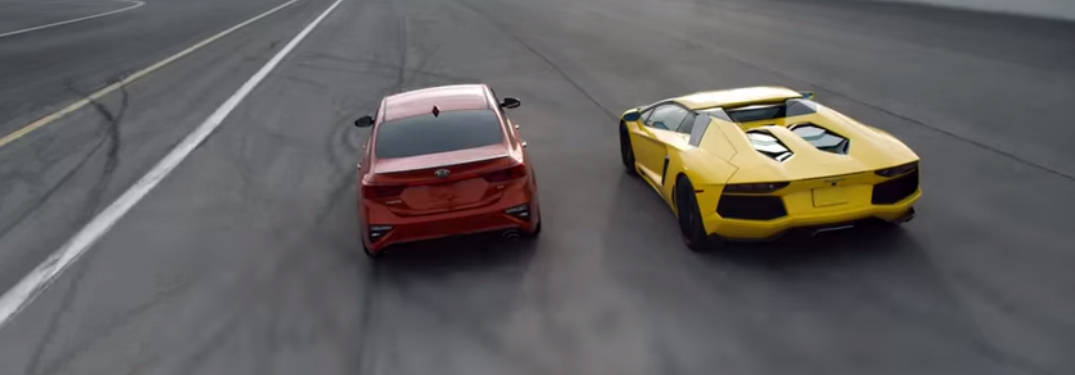 2019 Kia Forte and Lamborghini Aventador driving side by side on a race track