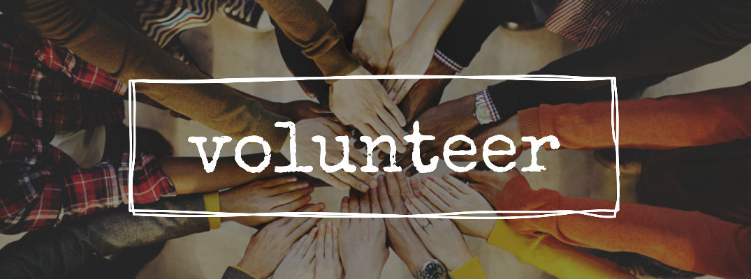 Volunteer with several hands in circle