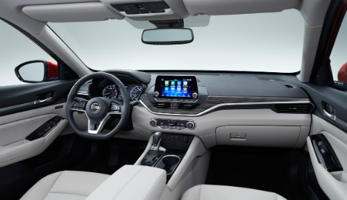 view inside the 2019 Nissan Altima showing steering wheel, dashboard with wood trim and touch screen display