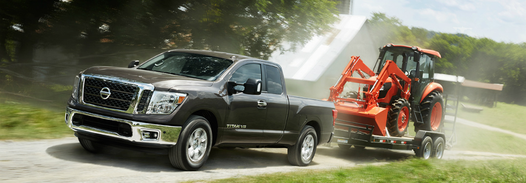 Nissan Titan towing a tractor on a trailer