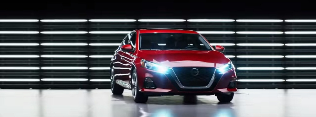 2019 Nissan Altima Front View of Red Exterior with Headlights on