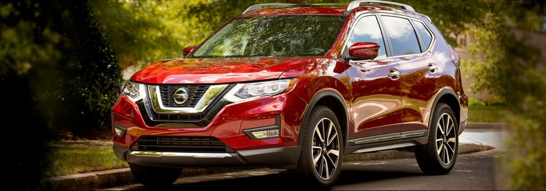 Red 2019 Nissan Rogue parked in a subrub in front of what may be a small river. Exterior angled front/side view.