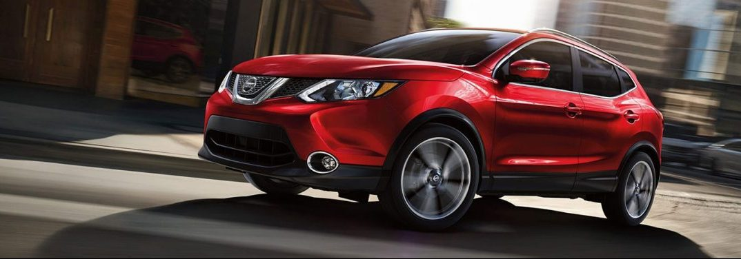 Red 2019 Nissan Rogue Sport cruises up a city street. Exterior front/side angled view.