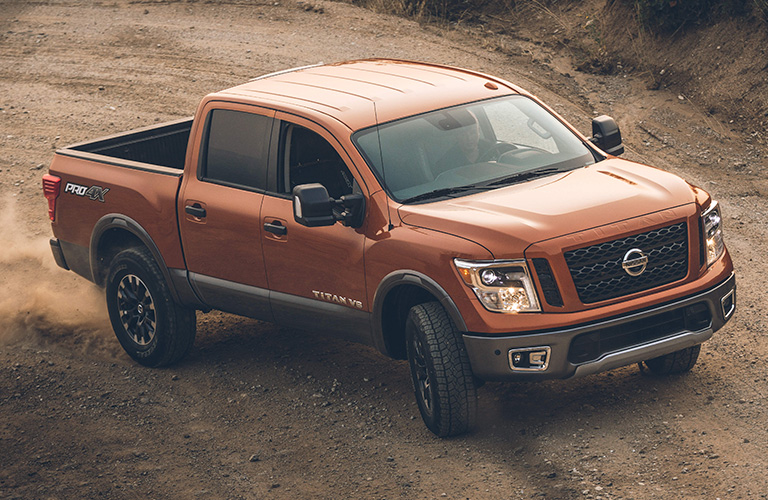 Brown 2019 Nissan Titan drives across dirt. Exterior side/front angled shot from a raised position.