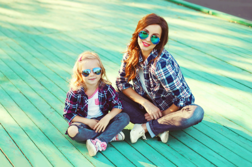 A mother and daughter sit beside each other on a green boardwalk.