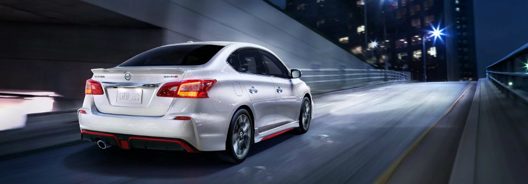 White 2019 Nissan Sentra NISMO drives out of an underground highway tunnel at night.