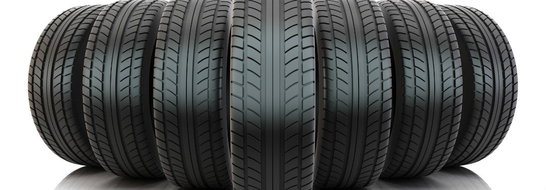 """Seven rubber tires stand proudly in a line, facing the camera head-on in a """"V"""" formation."""