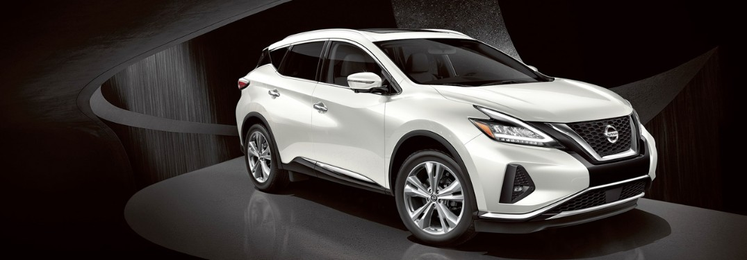 Front passenger angle of a white 2019 Nissan Murano on a dark background