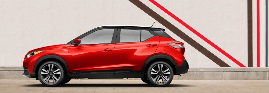 Red 2020 Nissan Kicks parked in front of building from exterior drivers side