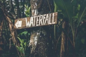 Sign in woods pointing arrow toward water fall