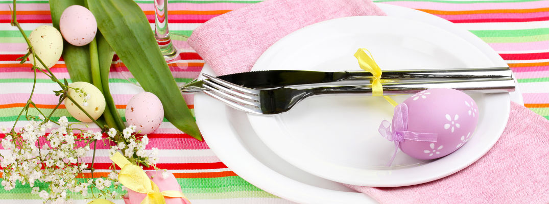 Easter Table Setting with colorful tablecloth and easter egg next to fork and spoon