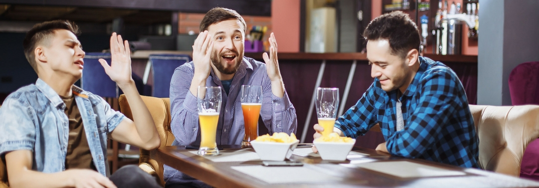 frustrated men watching sports at a bar