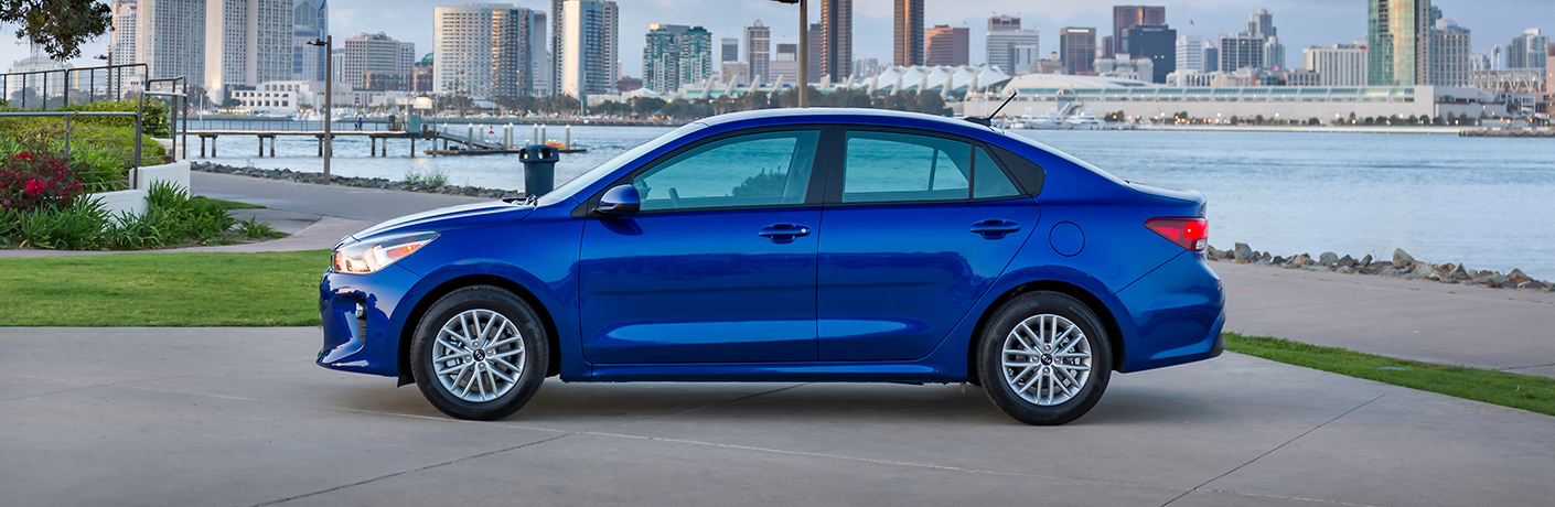 Exterior view of a blue 2018 Kia Rio parked in the city with water and skyscrapers in the background