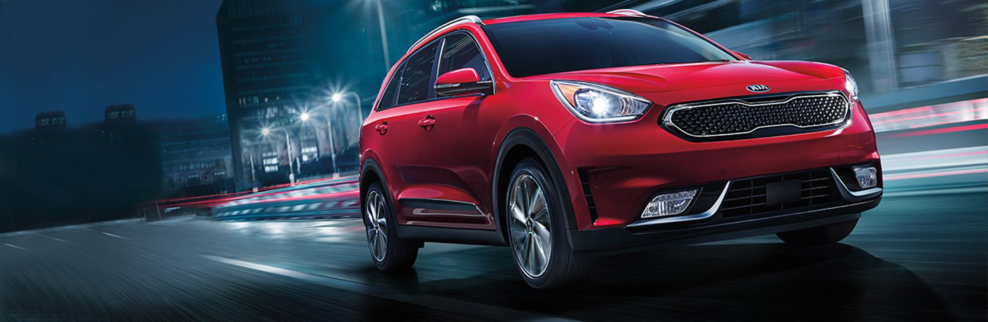 Exterior view of a red 2018 Kia Niro driving down a city street at night