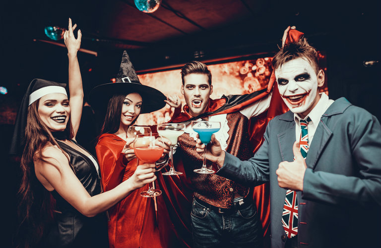 A group of adults in costume toasting with their drinks at a Halloween party