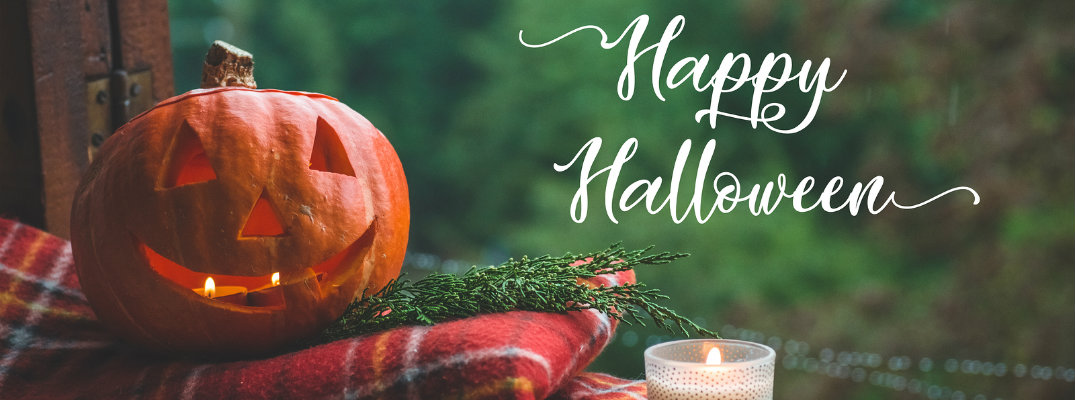 Pumpkin sitting on a flannel blanket with white Happy Halloween text to the right