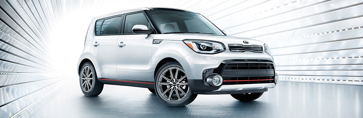 Exterior view of a white 2019 Kia Soul parked in a white showroom
