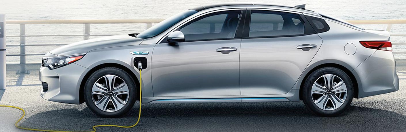 Exterior view of a silver 2018 Kia Optima Plug-In Hybrid plugged in and charging the electric motor battery