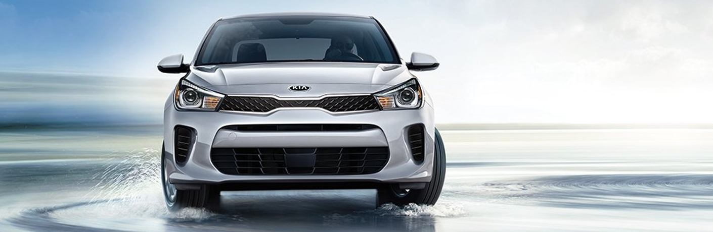 Exterior view of the front of a silver 2019 Kia Rio driving on the beach