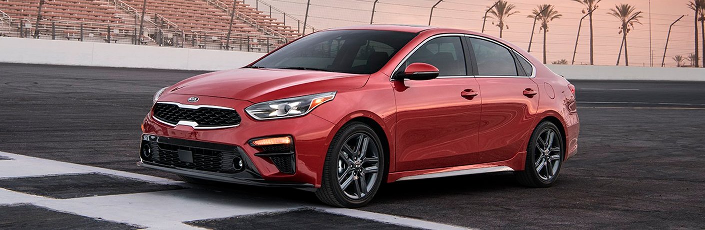 Exterior view of a red 2019 Kia Forte parked at the finish line of a race track